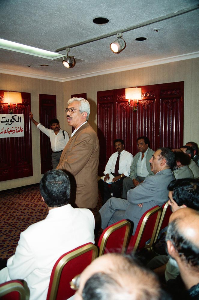September 7, 1990  Audience member Abdulmutalib Al-Kazemi, ex-Minister of Oil, speaking at first meeting of the Kuwaiti People's Movement. Seated next to him is Ali Al-Matrouk (in gray suit). Seated against the wall is Abdulrahman Al-Najjar (wearing tie) and beside him Najm Abdulkareem.