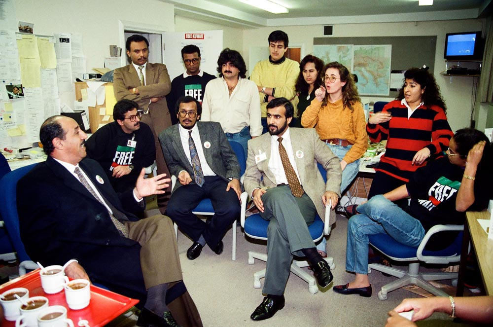 December 5, 1990  Kuwaiti Minister of Foreign Affairs (now Emir of Kuwait) Sheikh Sabah Al-Ahmad Al-Jaber Al-Sabah paid a surprise visit to FKC headquarters at Porchester Terrace. In a casual setting in the basement office of the Media Committee office, he discussed the nation's future and expressed optimism that returning home was imminent. He conveyed a message from the Emir of gratitude for the Committee's work. Seated (from left) are the Minister, Alaa' Al-Salah, Bader Al-Nashi, Khalid Al-Hajri, and Sheikha Iman Fahad Al-Sabah. Standing are (from left) the Minister's security guard, Ali Al-Mulaifi, Ibrahim Qabazard, Sheikh Majid Al-Sabah, Sheikha Anwar Al-Sabah, Dina Sultan, and Sundus Hamza Abbas. (See also .)