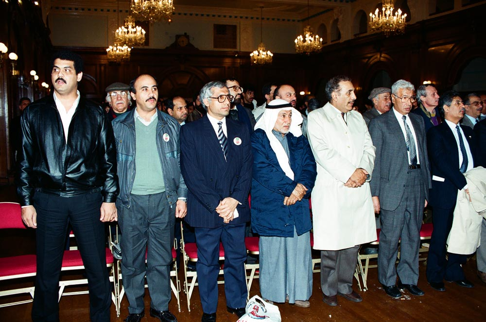 December 16, 1990  The audience at a packed Kuwait People's Committee event, which included speeches, poetry, and prayers. In the front row are (starting 2nd from left) Taleb Abu Al-Hasan, Dr. Abdulmohsen Jamal, Kazem Abdulhussein, Ali Al-Matrouk, Nouri Al-Kazemi, and Ambassador Ghazi Al-Rayes (extreme right). In the 2nd row are Khalid Khalaf (extreme left) and Dr. Yousif Shuhaibar (in purple sweater) behind the Ambassador. (See also .)