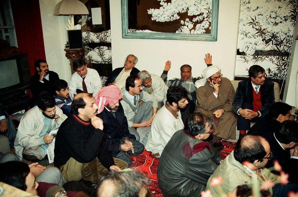 February 4, 1991  The participants at the KHC diwaniya packed the room. Seated on the couch are (extreme left) Mohamed Al-Naqi and (extreme right) Rashid Al-Zeer. Seated on the floor (in center) is Dr. Ahmad Jaf'ar Al-Kandari wearing gray vest.