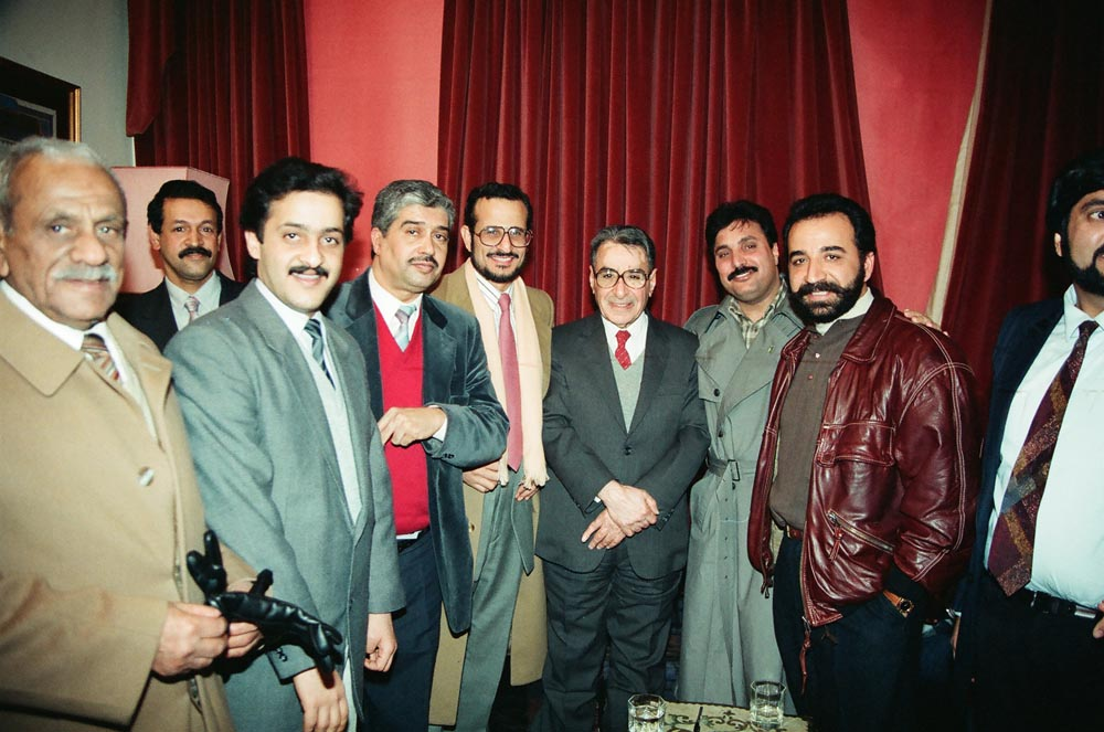 February 4, 1991  After his talk, Jassim Al-Sager (in red tie) posed with KHC diwaniya participants. Among them are Mubarak Al-Mutawa (in pink tie), Rashid Al-Zeer (in red vest), Abdulhameed Dashti (in brown jacket), and Ahmad Al-Houli (cut off on extreme right). In the back (on left) is Anwar Al-Hasawi.