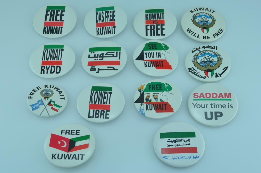 Campaign Buttons  FKC buttons are shown in 5 languages: Arabic, English, Welsh, French, and German. The button on the upper left depicts the first version of the official FKC logo. Virtually all buttons designed by Michael Lorrigan, Sam Bassan, and Ali Al-Mulaifi. The design process for campaign memorabilia involved creation by Lorrigan based on items and suggestions submitted by Bassan. Al-Mulaifi, an interior designer by profession with a good visual eye, was consulted when the others were close to the finished article. The next step was showing the items to the rest of the Media Committee members. If everyone liked the design, the item was manufactured. If not, adjustments were made. From start to finish, the process was speedy. The committee operated mostly autonomously, often had its own sources of funding, and rarely needed approval for its projects.